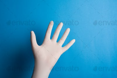 Hand with surgical glove on blue background