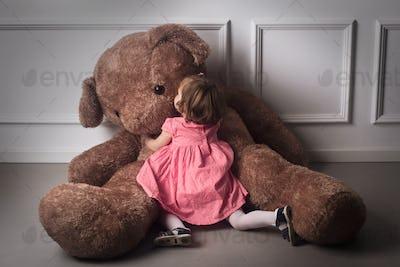Little girl hugging a big teddy bear