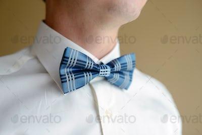 Groom is wearing a bowtie indoors