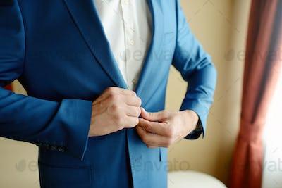 Groom is wearing a suit indoors