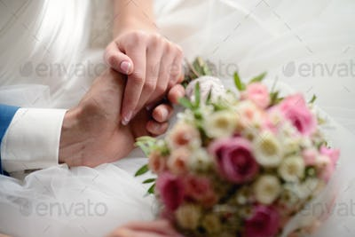 Wedding couple is holding hands