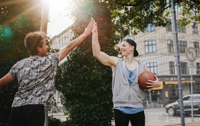 Friends giving high five after a game of streetball