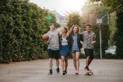 Happy teenage friends enjoying on basketball court