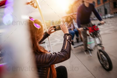 Woman photographing friends riding tricycle