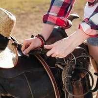 Saddle prepared for horse riding by young woman cowgirl