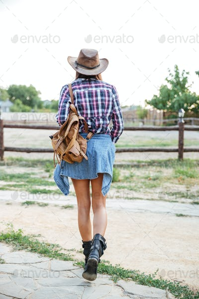 Back view of woman cowgirl with backpack walking on ranch