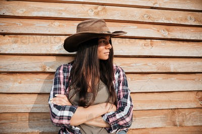 Beautiful young woman cowgirl in hat standing with arms crossed