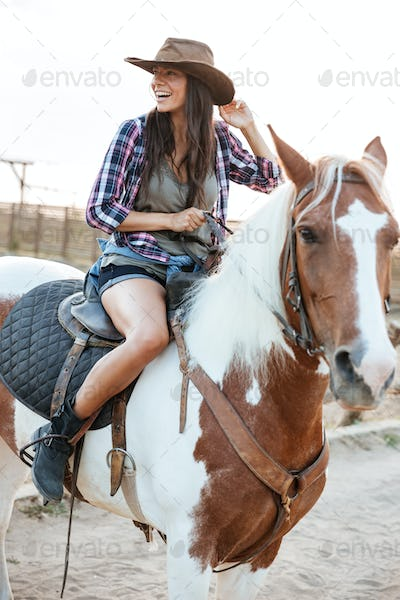 Cheerful woman cowgirl sitting and riding horse in village