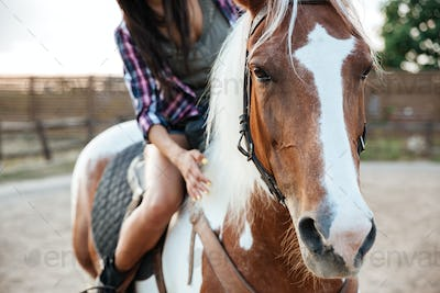 Woman cowgirl riding beautiful horse in village