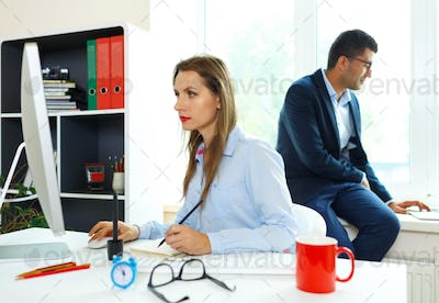 Beautiful young woman and man working from home