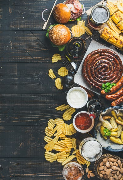 Octoberfest beer and snacks variety on dark scorched wooden background