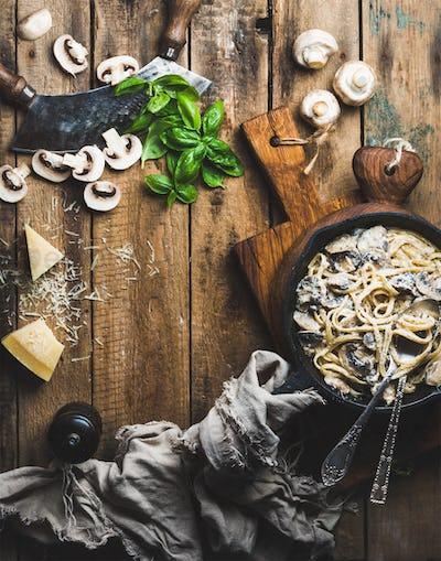 Creamy mushroom pasta spaghetti in cast iron pan, copy space