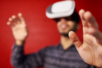 Millennial Indian man exploring space with virtual reality glass