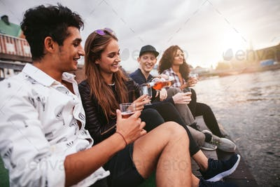 Friends sitting outdoors on jetty and having drinks