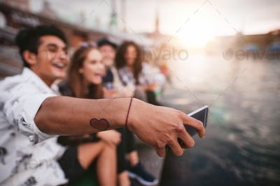 Young man with friends taking selfie by the lake