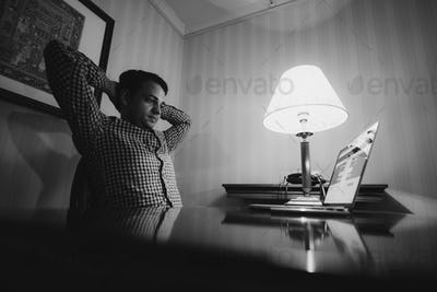 frustrated young business man working on laptop computer at office. Black and white photo.
