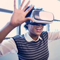 Cool millennial black woman exploring virtual reality glasses in an open-concept space