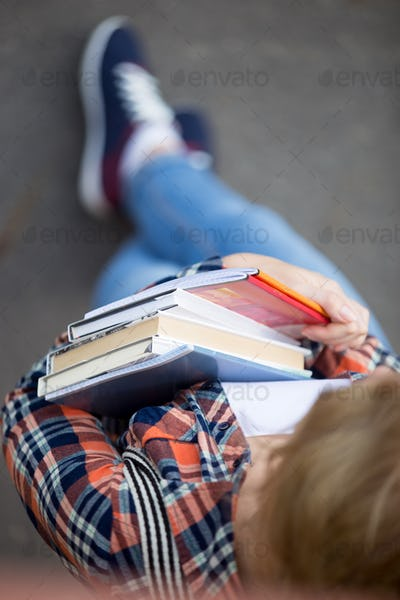 Student girl with a heap of textbooks and notebooks