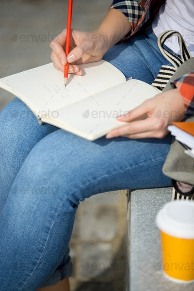 Student lady writing in an open notebook with a pencil