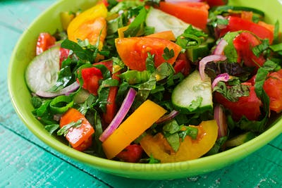 Fresh salad of tomatoes, cucumbers, peppers, arugula and red onion