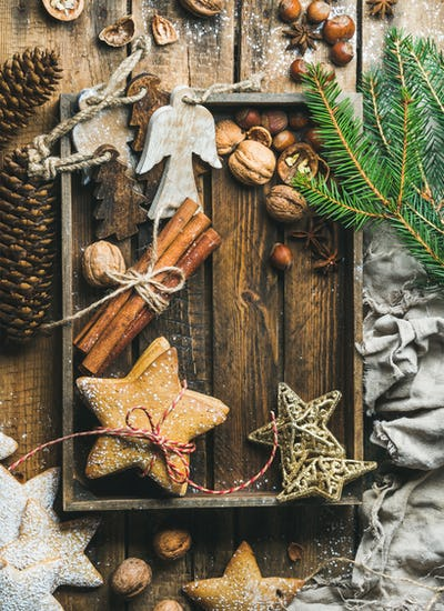 Wooden tray with cookies, decorative angels and stars, spices, nuts
