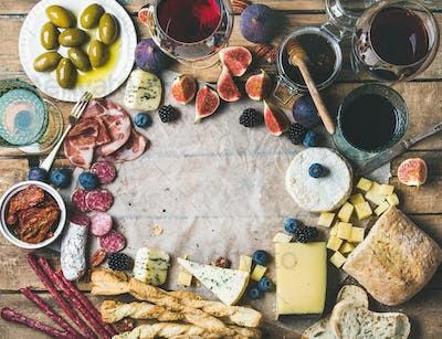 Wine and snack set with wines, meat, bread, olives, fruits