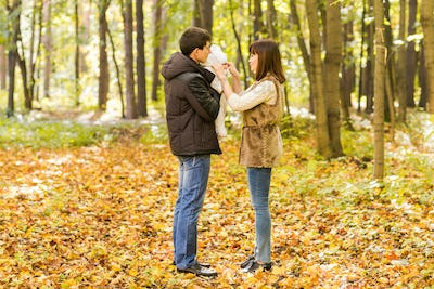 smiling couple with baby in autumn park