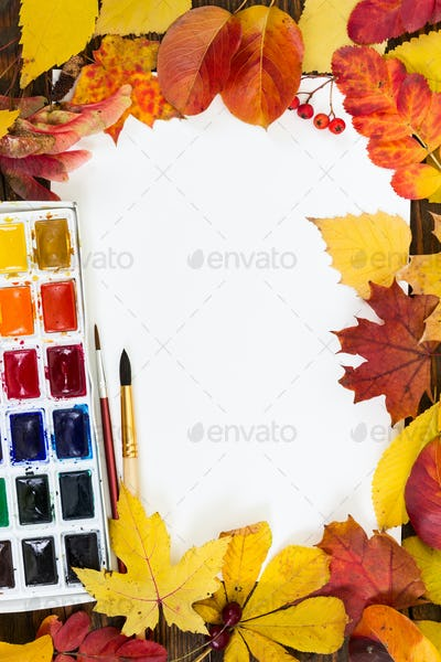Composition with sheet of white paper, paints, brushes and autum