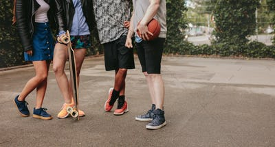 Group of people standing with basketball and skateboard