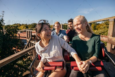 Young friends riding roller coaster
