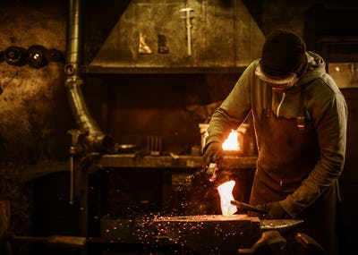 The blacksmith with brush handles the molten metal on the anvil in smithy