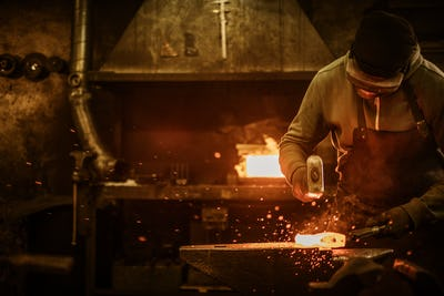 The blacksmith forging the molten metal on the anvil in smithy