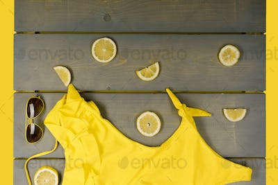 Yellow one-Piece swimsuit, aviator sunglasses between parts of lemons on grey wooden board.