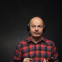 Elderly man with headphones listening to music with displeasure.