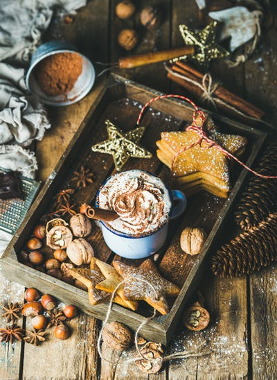 Mug of hot chocolate, gingerbread cookies, nuts in wooden tray