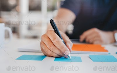 Business man writing on an adhesive note