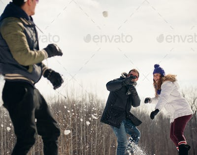 Group of friends enjoying a snowball fight in the snow in winter