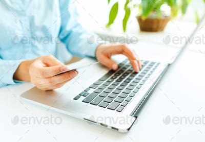 Hands using laptop and credit card