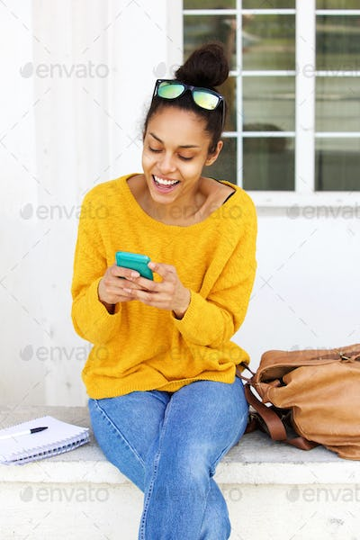 Cheerful young woman sitting outside using cellphone
