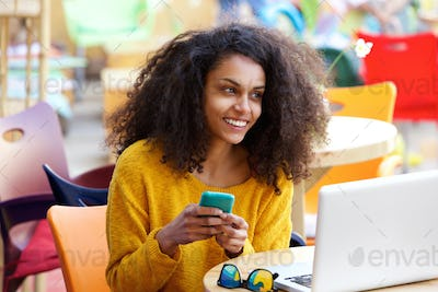 Cheerful woman at outdoor cafe with mobile phone