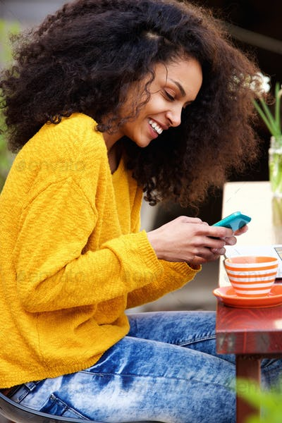 Cheerful woman reading text message on cellphone at cafe