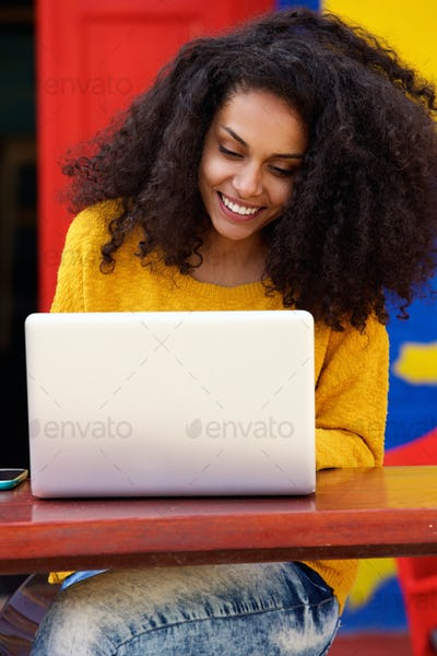 Smiling black woman using laptop at cafe