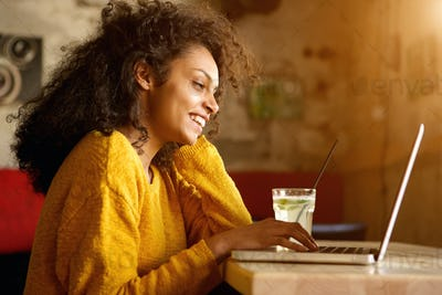 Cheerful young woman working on laptop in cafe