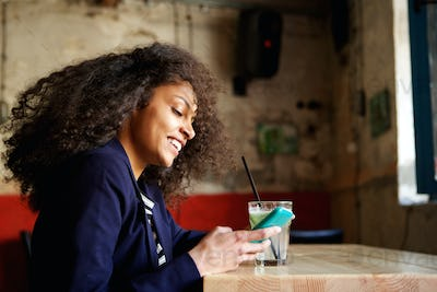 Smiling young lady relaxing in a coffee shop with mobile phone