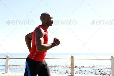 African man jogging on seaside promenade