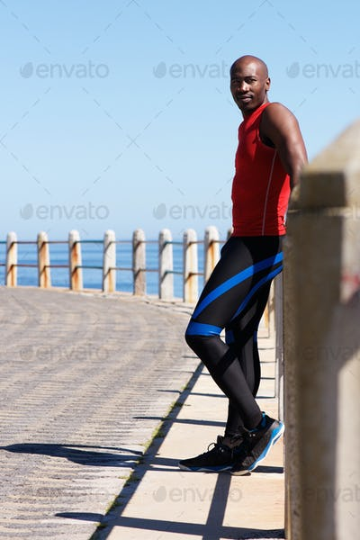 Fit young african man standing at seaside promenade