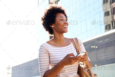 Young woman walking with cell phone and purse in the city