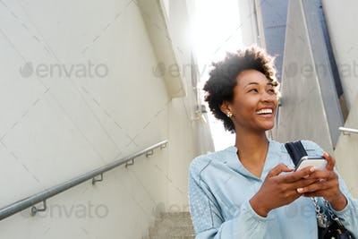 Young black woman on steps with mobile phone