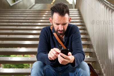 Mature man sitting on stairs using mobile phone