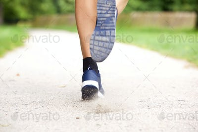 Female runner shoes on path